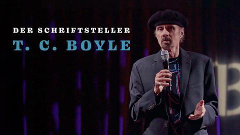 T.C. Boyle steht mit Mikrofon in der Hand auf der Bühne. Schriftzug: Der Schriftsteller T.C. Boyle.
