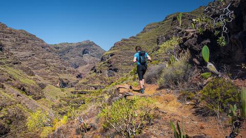 Ein Wanderer läuft durch Gebirge.