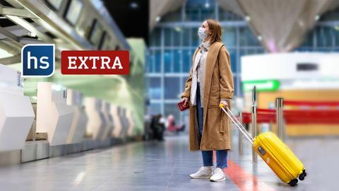 Eine junge Frau steht mit ihrem kleinen gelben Koffer im Flughafen und liest eine Infotafel. Logo: hs extra.