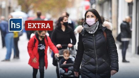 Frau mit Mundschutz läuft durch eine Einkaufsstraße.