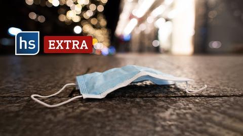 Eine Schutzmaske liegt am frühen Morgen auf dem Bürgersteig. Es ist noch dunkel. Schriftzug: hx extra.
