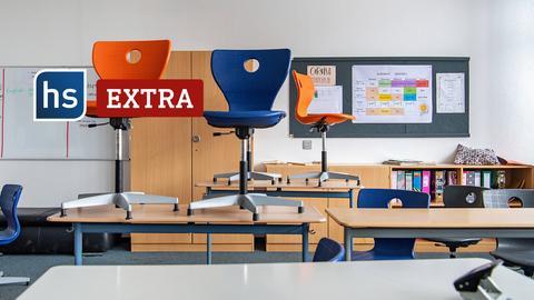 Vier bunte Stühle stehen auf einem Tisch in einem Klassenzimmer. Schriftzug: hs extra.