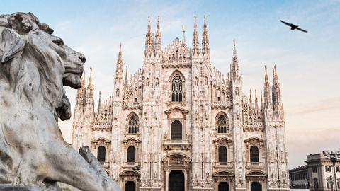 Ein steinerner Löwe links im Bild, der auf den Mailänder Dom zu schauen scheint.