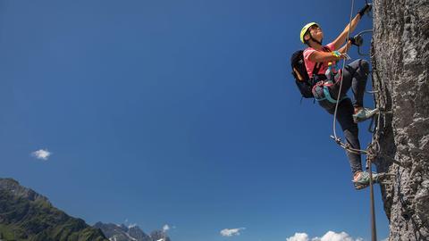 Eine Frau klettert gesichert an einem Berg hoch. Text: Mindelheimer Klettersteig.
