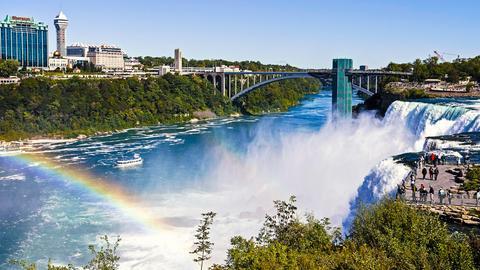 Blick auf die Niagarafälle und die gegenüberliegende Umgebung. Ein Regenbogen erscheint durch das Zusammenspiel des feinen Wassernebels und des sonnigen Wetters.