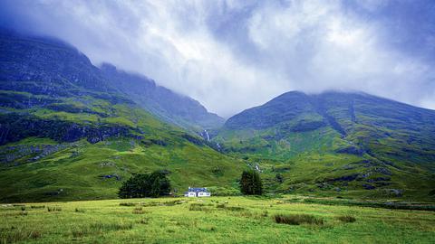 Graue Wolken über Glen Coe. Ein einziges Haus steht am Fuß des Berges.