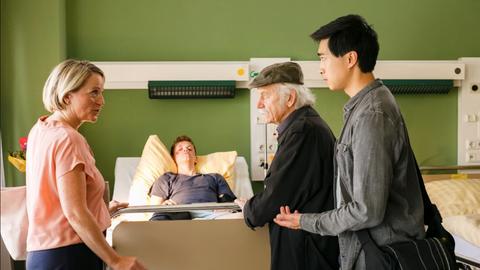 Hui Ko (Aaron Le, r.) und Edwin Bremer (Tilo Prückner, 2.v.r.) statten Oskar Ribenbrok (Carl Benzschawel, 2.v.l.) eine Krankenbesuch ab und treffen dort auf seine Mutter Katja Ribenbrok (Isabel Schosnig, l.).