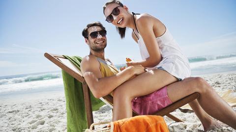 Ein Pärchen reibt sich am Strand mit Sonnencreme ein