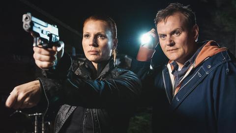 Die Hauptkommissare Lisa Marx (Elisabeth Brück) und Jens Stellbrink (Devid Striesow) im Einsatz. Lisa Mark zielt mit ihrer Pistole auf etwas außerhalb des Bildes. Jens Stellbrink hält neben ihr eine Taschenlampe hoch.