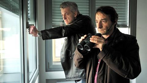 Die beiden Kommissare bei der Observation an einem Fenster.