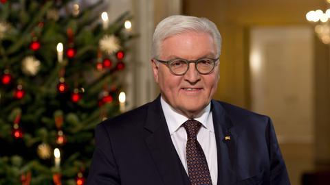 Frank Walter Steinmeier mit geschmücktem Weihnachtsbaum im Hintergrund.