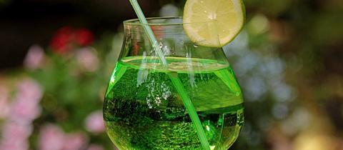 Ein grüner Waldmeister-Cocktail mit Strohhalm und einer Limetten-Scheibe.