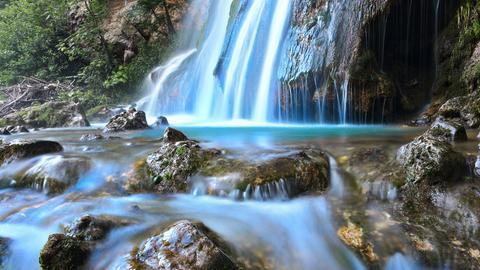 Wasserfall der in einen Fluss mündet.