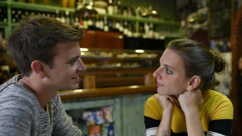 Ein Mann und eine Frau unterhalten sich in einer Bar.