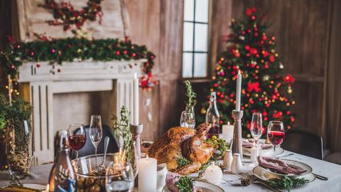 Weihnachtlich gedeckter Tisch mit einem Truthahn sowie Weihnachtsbaum im Hintergrund.